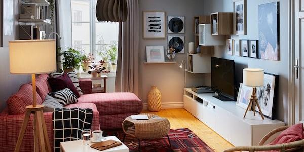Mały pokój dzienny z perskim dywanem w czerwone wzory, czerwoną sofą, szarymi zasłonami, rattanowym fotelem i nastrojowym oświetleniem.