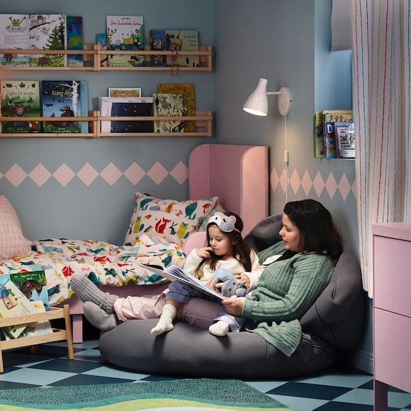 Mama czytająca książkę dziecku w pokoju dziecięcym.