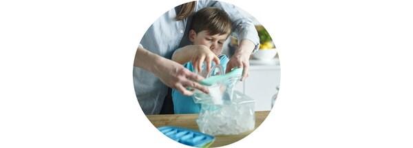 Mama z synkiem napełniają torebki strunowe ISTAD kostkami lodu.