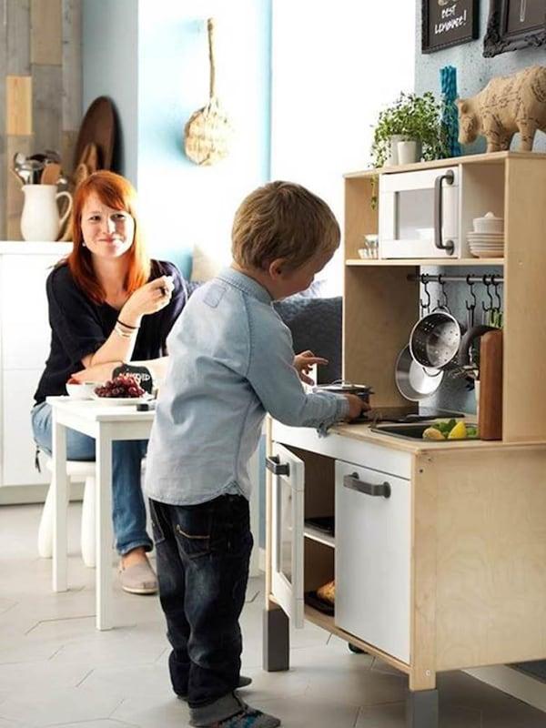 Mamička sleduje svoje dieťa pri hre s detskou kuchynkou DUKTIG.