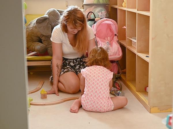 Maminka si hraje v děstském pokoji se svojí dcerou.