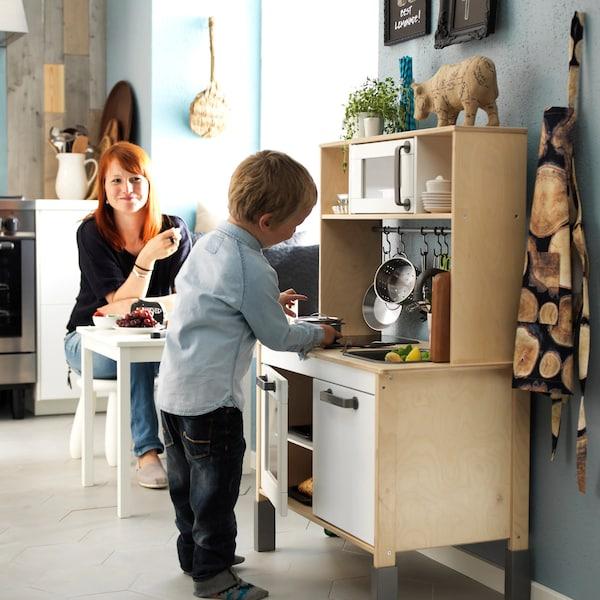 Maminka sleduje své dítě při hraní s dětskou kuchyňkou.