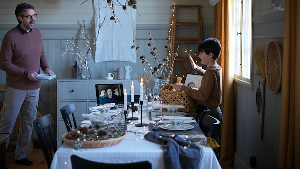 Man and boy setting a holiday table while speaking with man via video call.