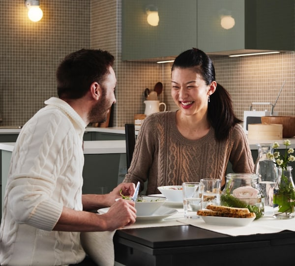 Man and women sitting down in new home having dinner.