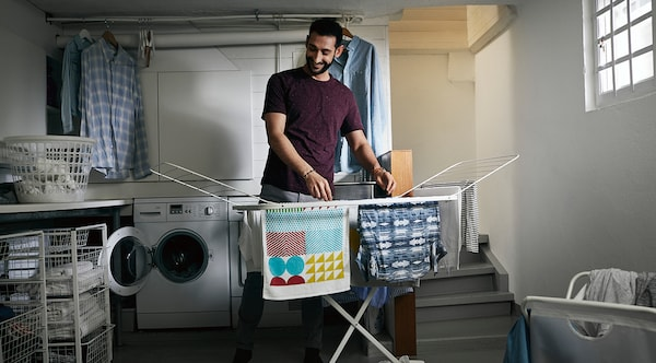 Man drying laundry on a MULIG drying rack
