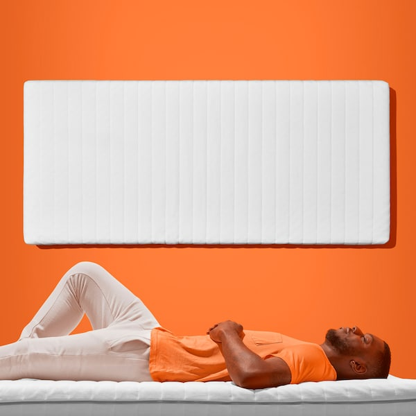 Man in an orange t-shirt laying on a mattress in front of an orange wall with a mattress hanging above him ont he