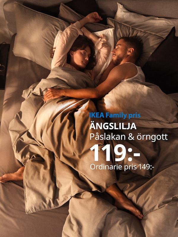 Man och kvinna håller om varandra i en säng där ÄNGSLILJA påslakanset används