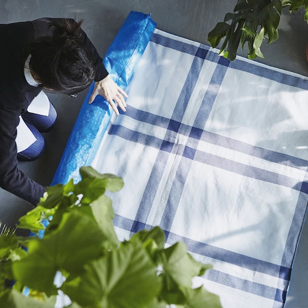 Man rolling up a picnic blanket made from IKEA blue bags