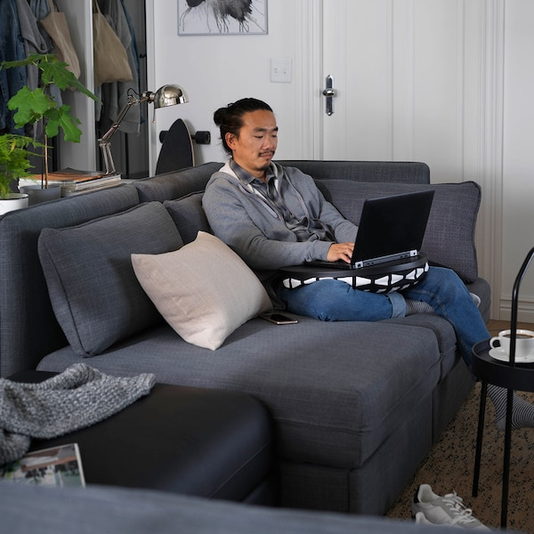 Man seated on a grey sofa, working on a computer placed on a laptop support.