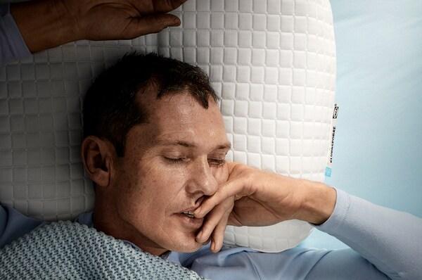 Man slaapt op zijn rug met zijn hoofd op een IKEA KLUBBSPORRE ergonomisch kussen.