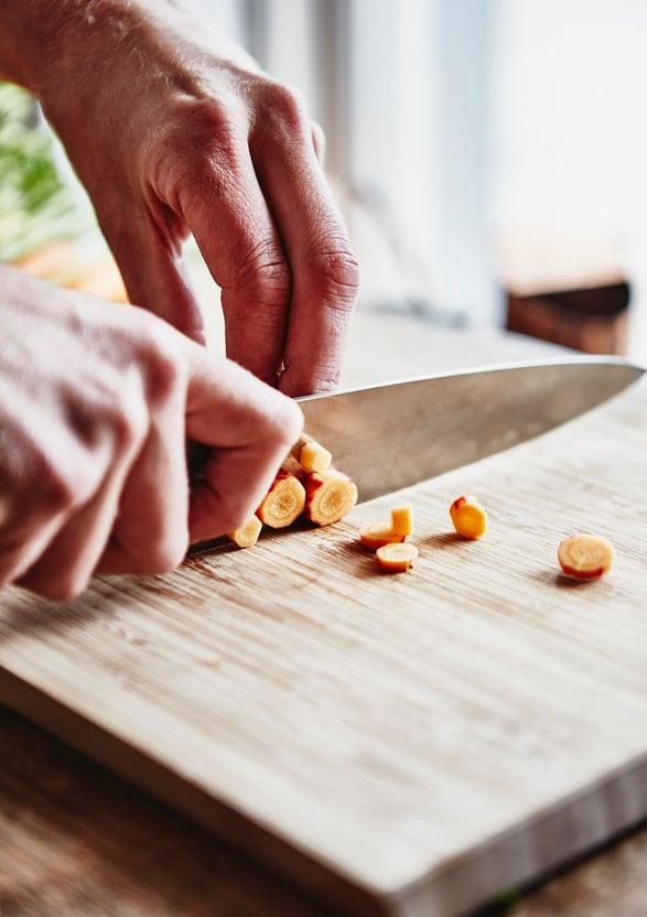 Man snijdt wortel op snijplank