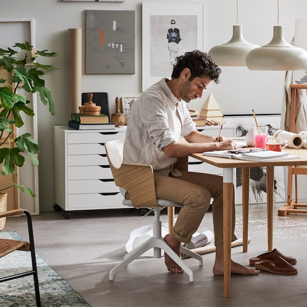 Man som sitter och jobbar hemifrån vid ett bord.
