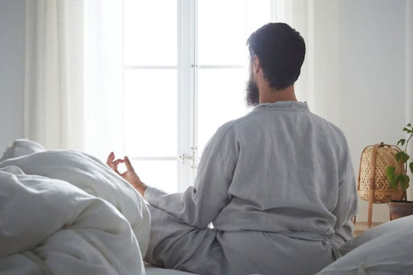 Man waking up with some yoga, natural fiber lamp and plants