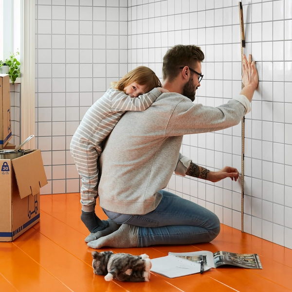 Man with young daughter measuring kitchen wall