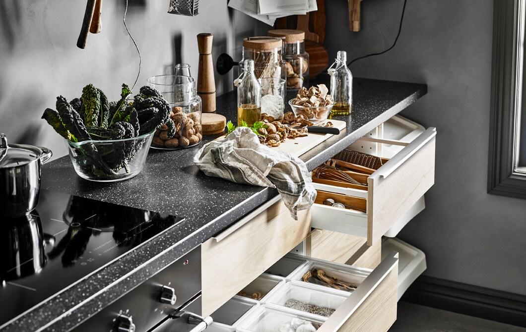まな板ののったキッチンワークトップと透明のガラス製の収納ビンとアッシュ扉のある開いた引き出し