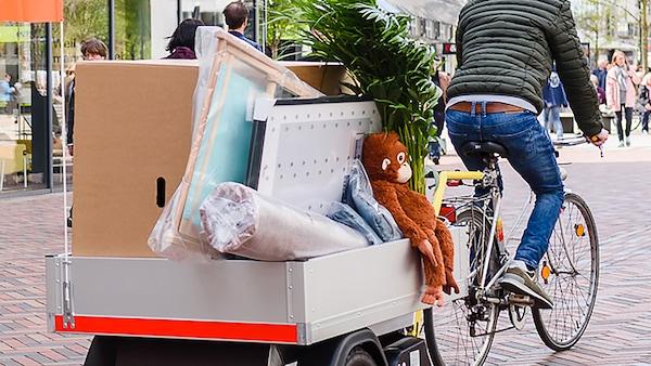 Mand cykler på gade med en trailer fyldt med produkter fra IKEA.