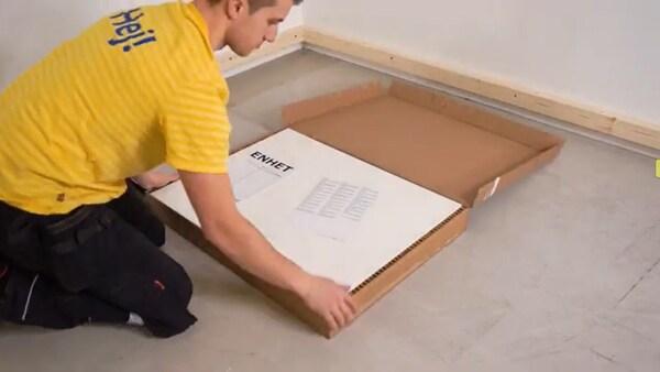 Mand i gul t-shirt er gang med at installere ENHET køkken.
