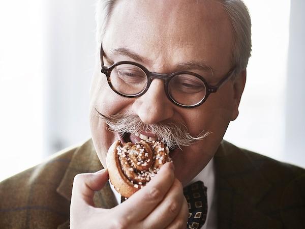 Mand med skæg og briller der spiser en kanelsnegl.