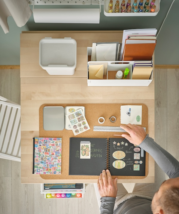 Mand sidder ved et bord, der er indrettet til at lave scrapbøger. Der ligger tilbehør på SUSIG skriveunderlag og i KVISSLE skrivebordsopbevaring.