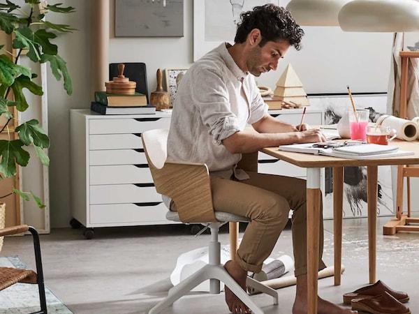 Mann som sitter å jobber hjemmefra.