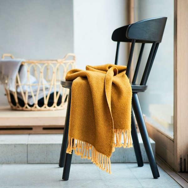 Manta cálida y suave OMTÄNKSAM fabricada en 100% lana virgen. Se muestra en color amarillo contra una silla negra.