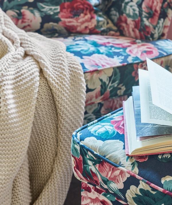 Manta IKEA INGABRITTA de color claro colgando de un sofá con estampado floral, cerca de un reposapiés con un libro abierto sobre él.