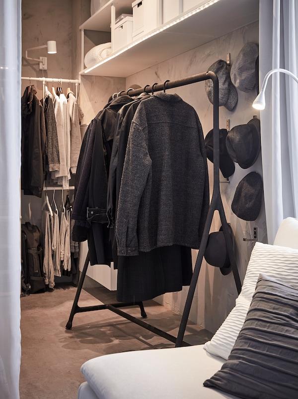 Manteaux et anoraks accrochés à un portant TURBO en noir. Robuste, il convient aux vêtements les plus lourds.