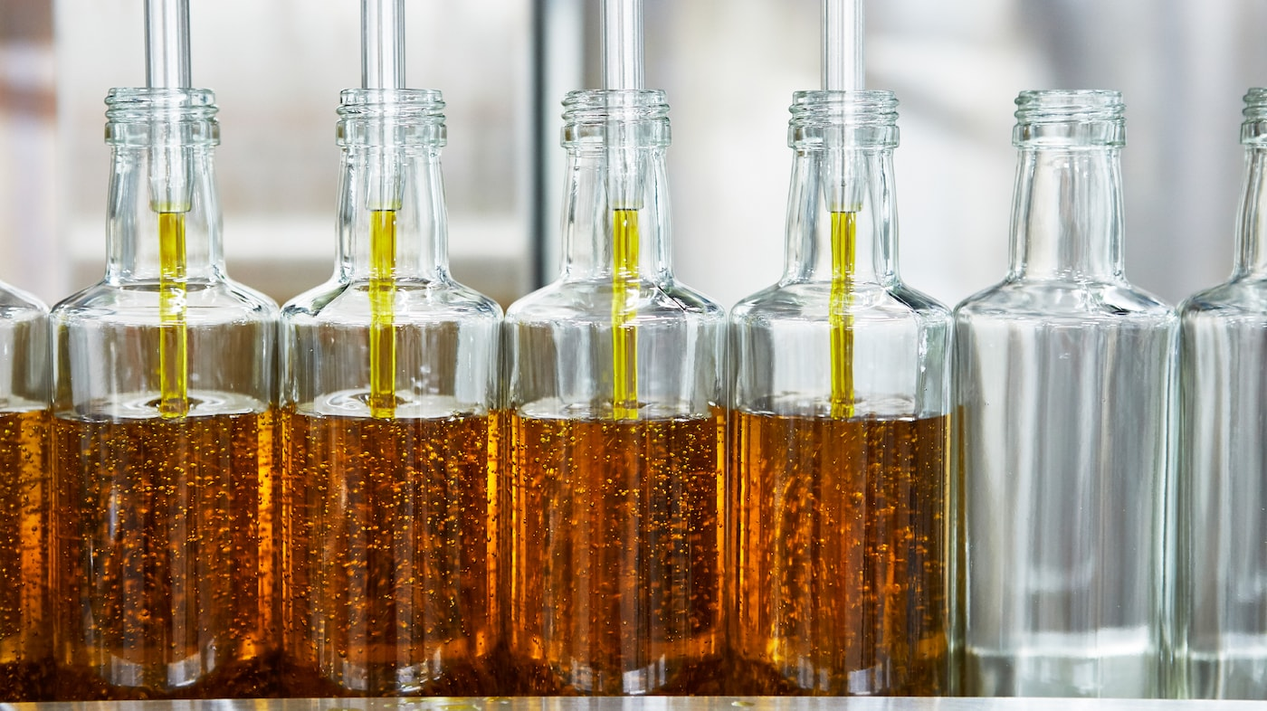 Many glass bottles standing side by side are being filled with organic, golden yellow IKEA SMAKRIK rapeseed oil.