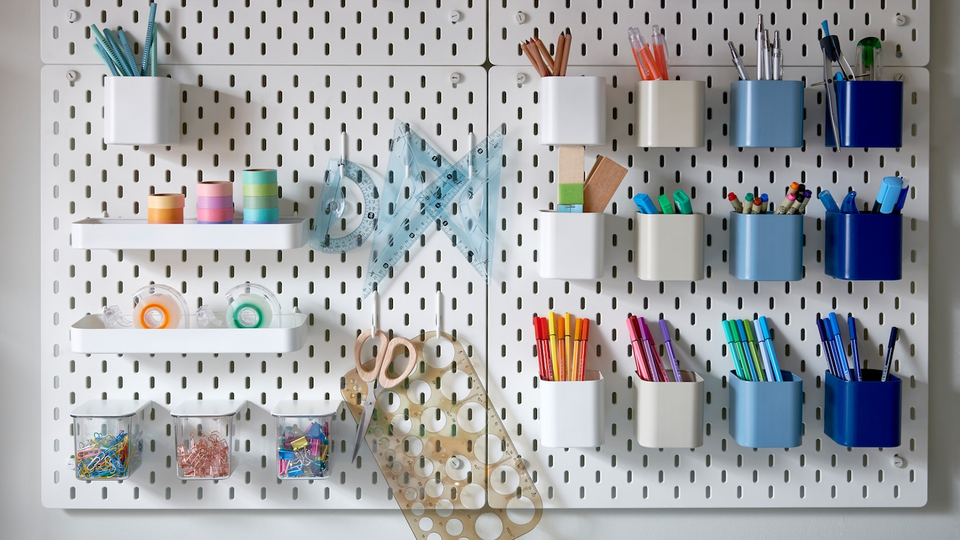 Many white pegboards with holes holding differently coloured containers storing colourful pens, paper clips and tape.