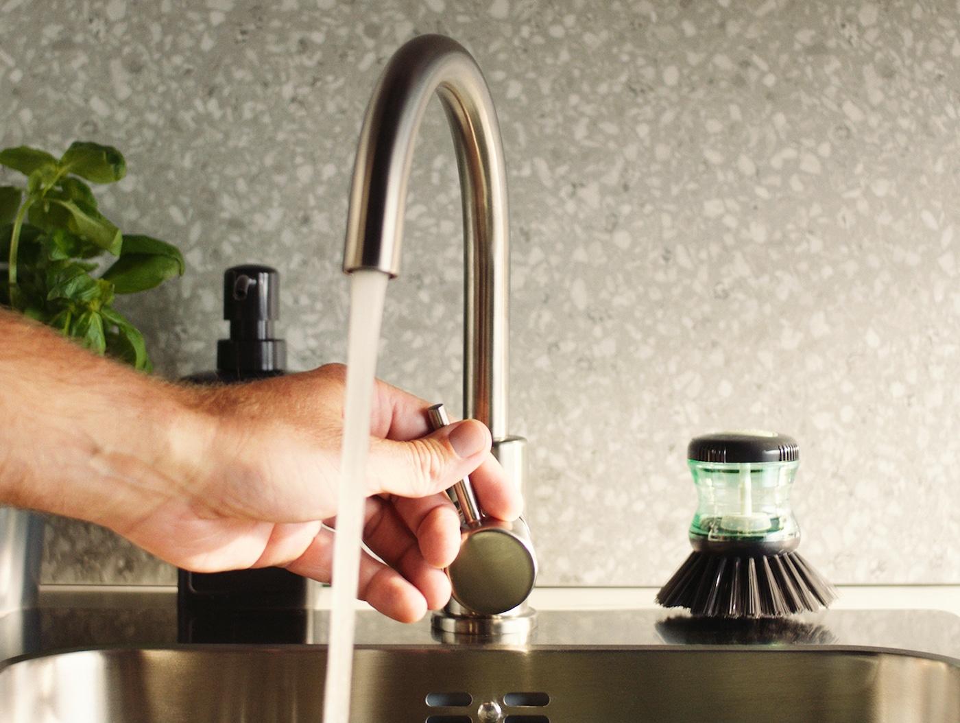 Mão a ajustar o caudal de água de uma torneira de cozinha GLYPEN em aço inoxidável, ao lado de uma escova para lavar a loiça TÅRTSMET.