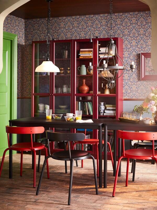 Masă de sufragerie TOMMARYD cu scaune YNGVAR de diferite culori înaintea a două vitrine roșii.