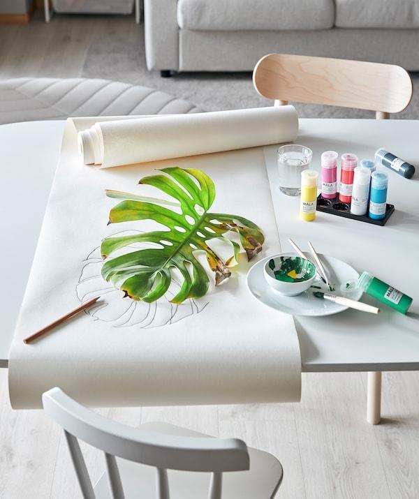 Masă în camera de zi aranjată pentru o sesiune artistică bazată pe folosirea plantelor: Vopsea MÅLA, hârtie  de desen și o frunză MONSTRERA parțial uscată.
