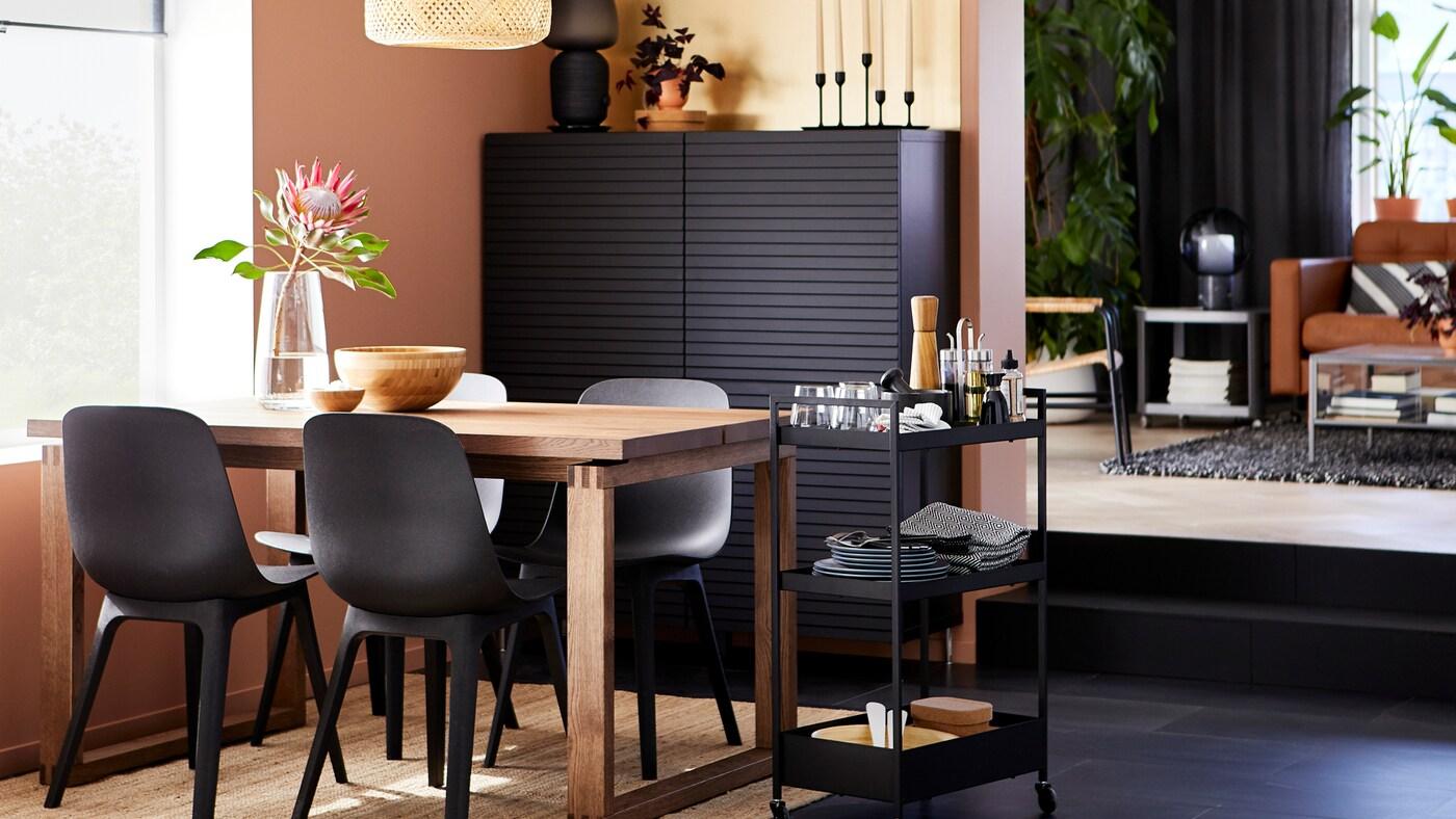 Masă pentru sufragerie MÖRBYLÅNGA din furnir de stejar cu scaune ODGER negre lângă o fereastră, cu un corp negru și un cărucior pe care se află veselă.