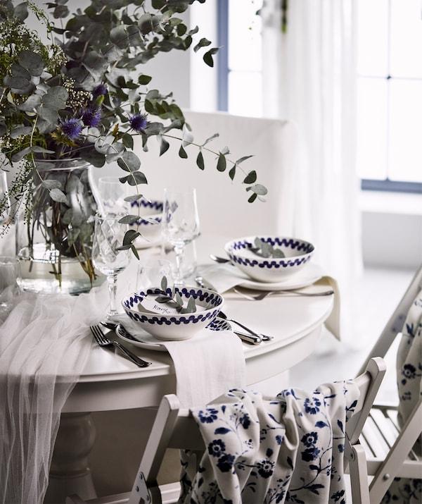 Masă rotundă festivă, albă, cu un buchet de flori sălbatice într-o vază de sticlă, și boluri și farfurii albe și albastre.