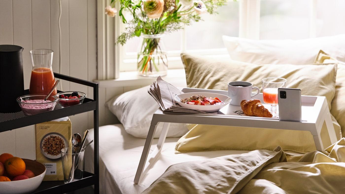 Mat på et trillebord og frokost servert på et hvitt KLIPSK sengebord på ei seng redd opp med ÄNGSLILJA sengetøy.