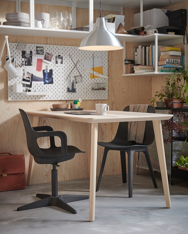 Matbord i trä med två ODGER stolar i antracit: en vanlig stol och en skrivbordsstol med armstöd.