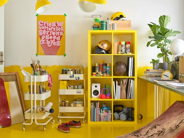 Match a yellow KALLAX shelving unit and two white RÅSKOG trolleys for a lot of flexible storage space in happy colours.