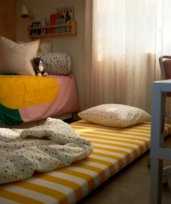 Matelas, oreiller et couette installés au sol à côté du lit. Lumière tamisée et rideaux tirés.