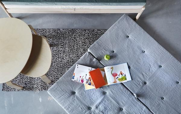 Materac leżący na podłodze obok stolika do kawy i sof.
