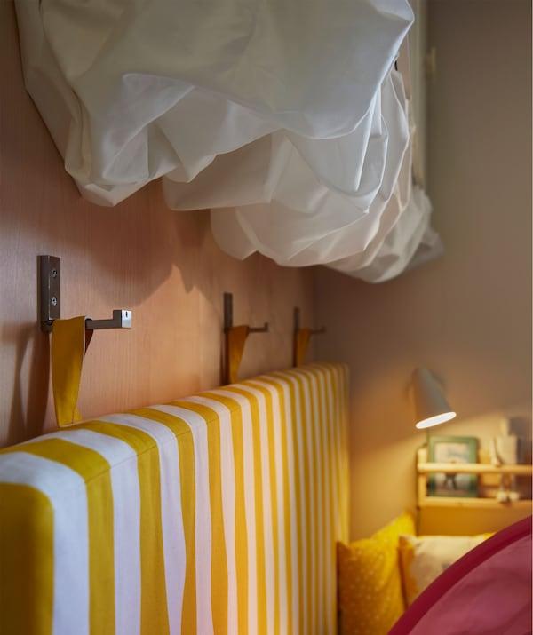 Materac zawieszony na haczykach na ścianie obok łóżka. Biała tkanina przymocowana pod szafką ścienną i tworząca kształty przypominające chmury.