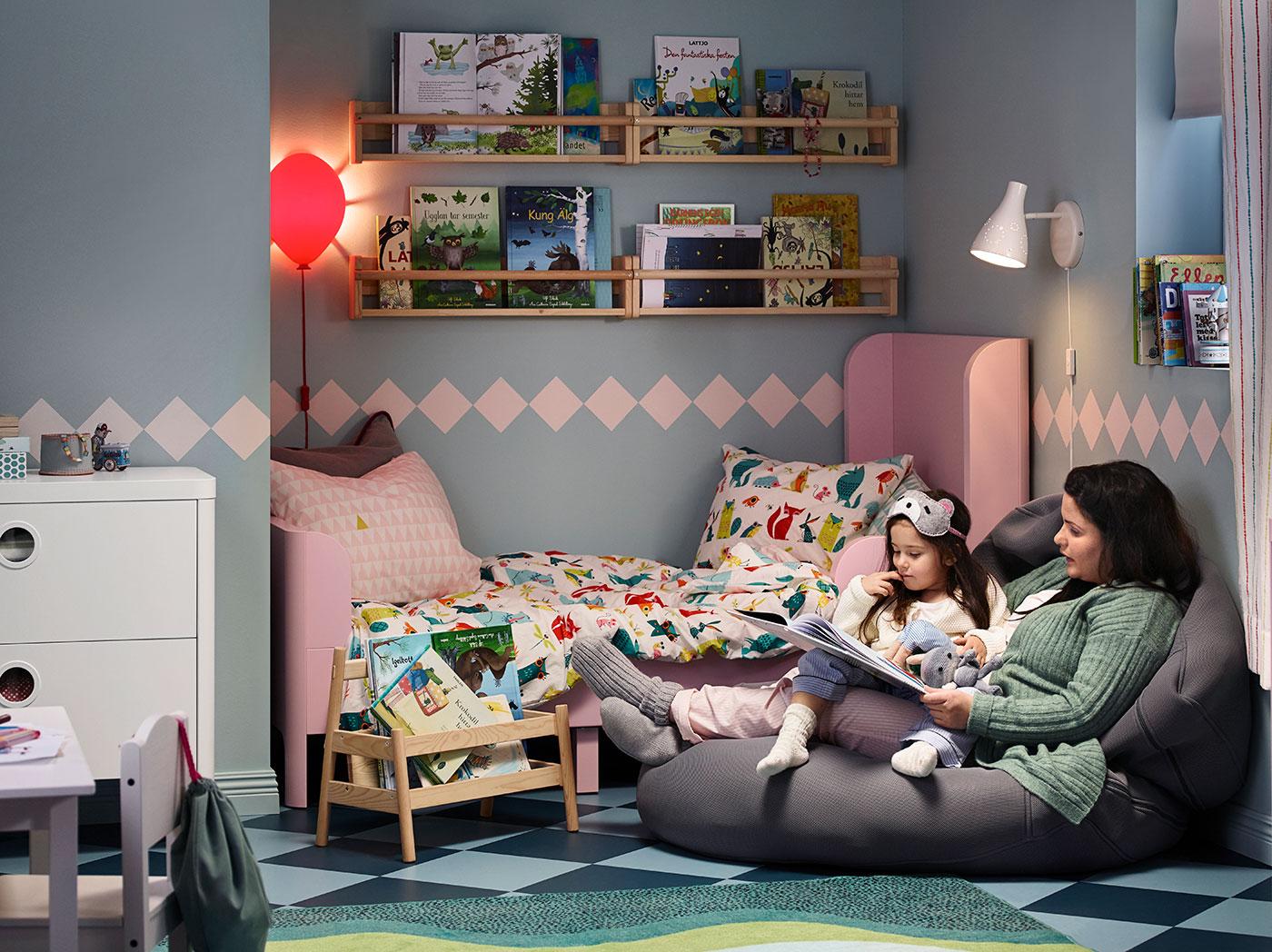 Matka a její malá dcera leží na křesle u postele a čtou pohádky na dobrou noc.