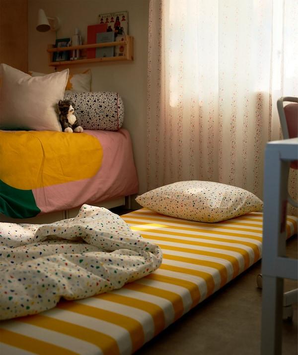 Matrac s vankúšom a paplónom na zemi vedľa detskej postele s tlmeným svetlom a zatiahnutými závesmi.