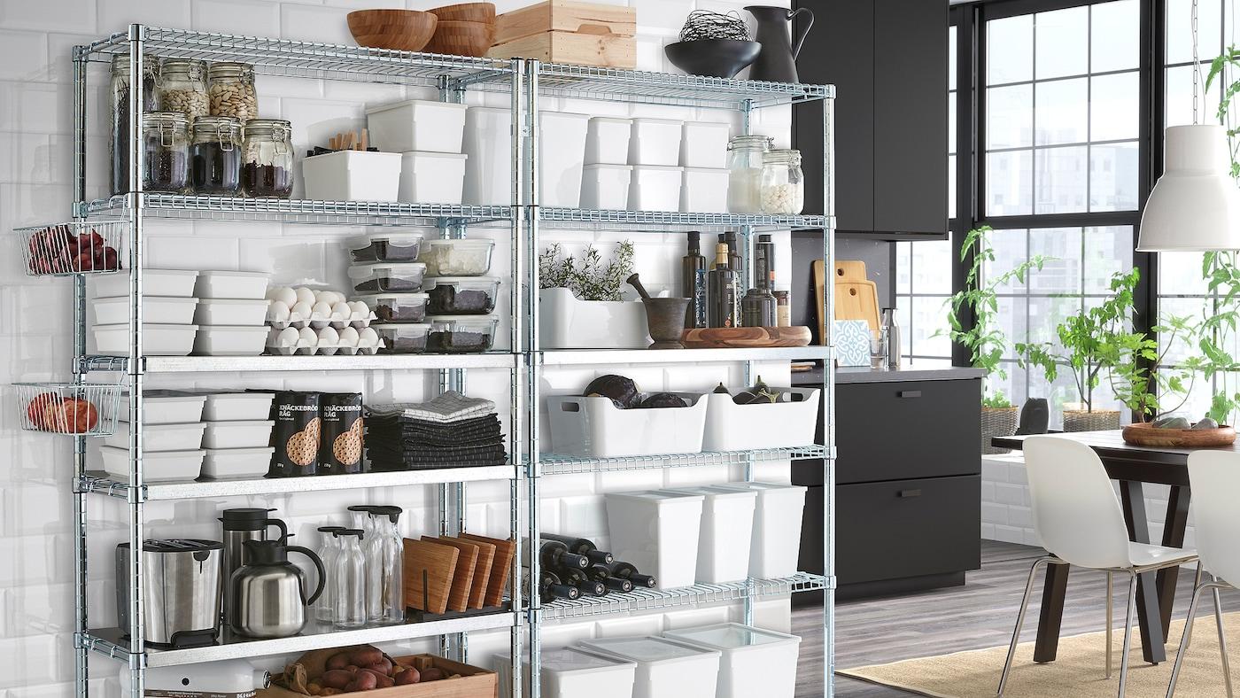 Matvarer og kjøkkenutstyr på to galvaniserte hylleseksjoner foran en hvit flisvegg med et mørkegrått kjøkken i bakgrunnen.