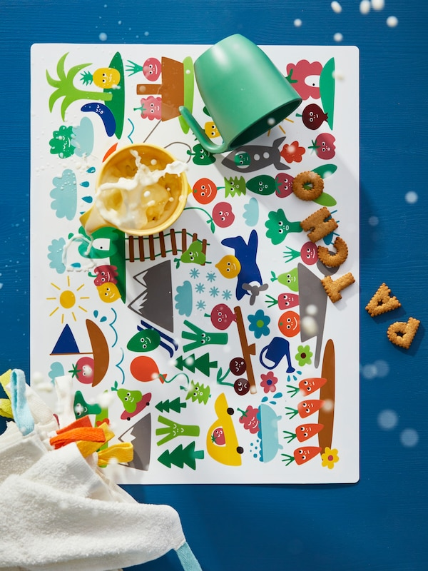 MATVRÅ kids place mat with colourful vegetable figures and children's plastic beakers with flying milk, biscuits and cloths.