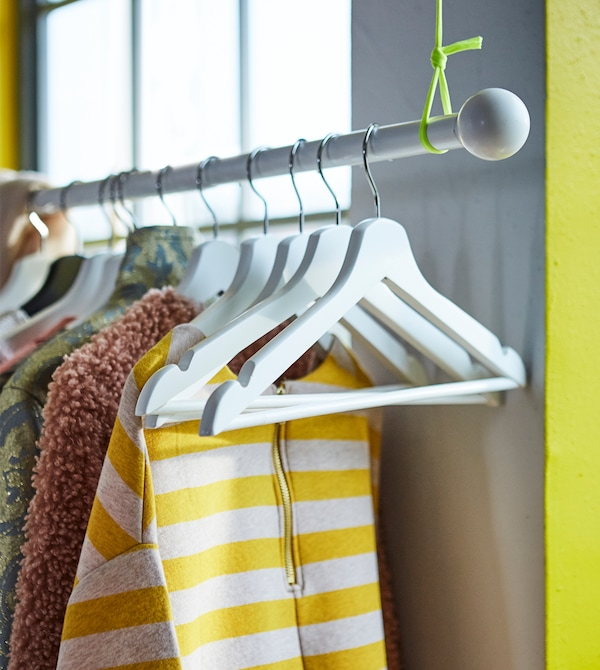 Maximise your storage space in a small bedroom. Attach a curtain rod such as IKEA HUGAD curtain rod to the ceiling, then hang up your favourite clothes!
