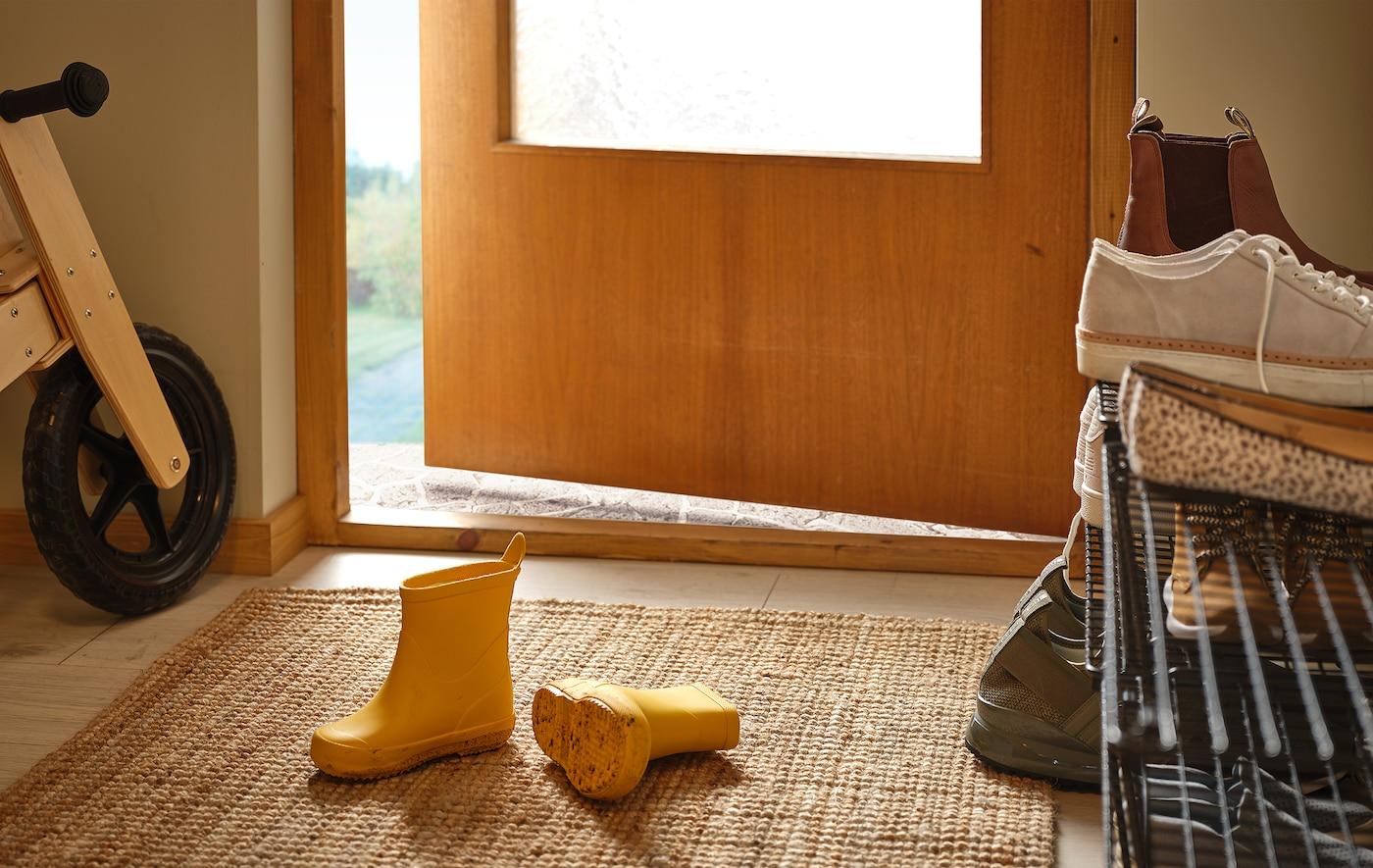 مدخل به بوتات أطوال مطاطية طويلة على سجادة، ورف أحذية ممتلئ على الجنب، ودراجة أطفال خشبية بمحاذاة الحائط.