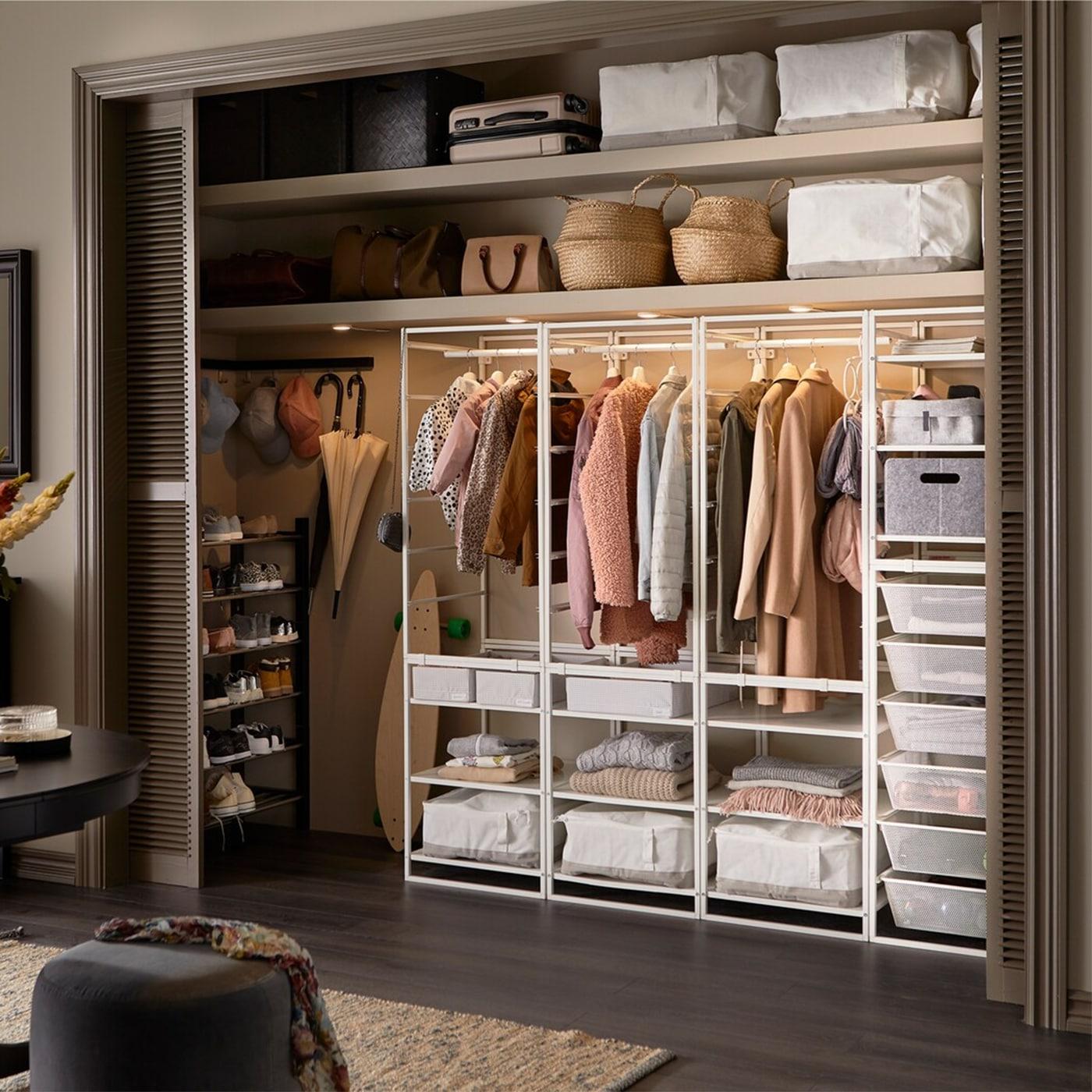 مدخل واسع مع دولاب ملابس مدمج مع نظام تخزين JONAXEL بلون أبيض، وأكياس تخزين بيضاء وإضاءة من الداخل.