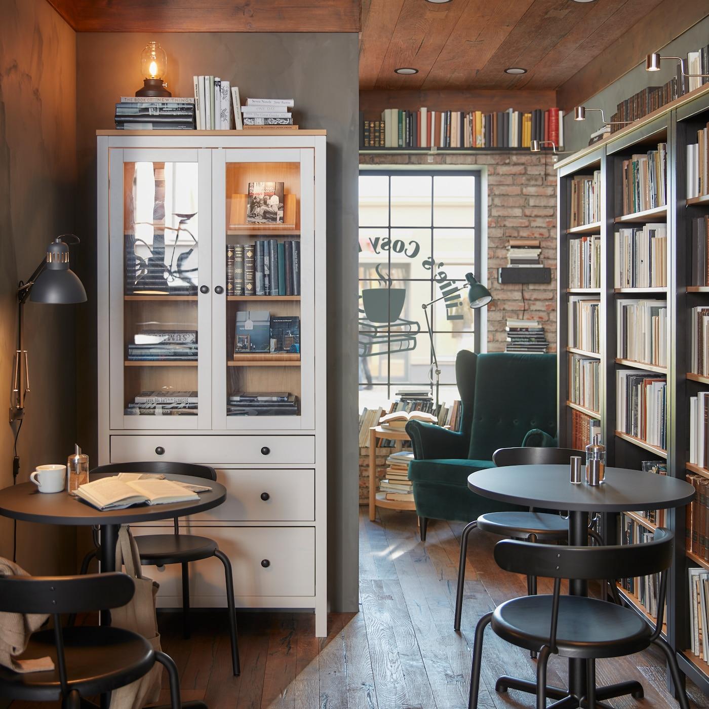 Меблированное кафе со множеством книг в шкафах, софитами и креслами с высокой спинкой, обитыми зеленым бархатом.