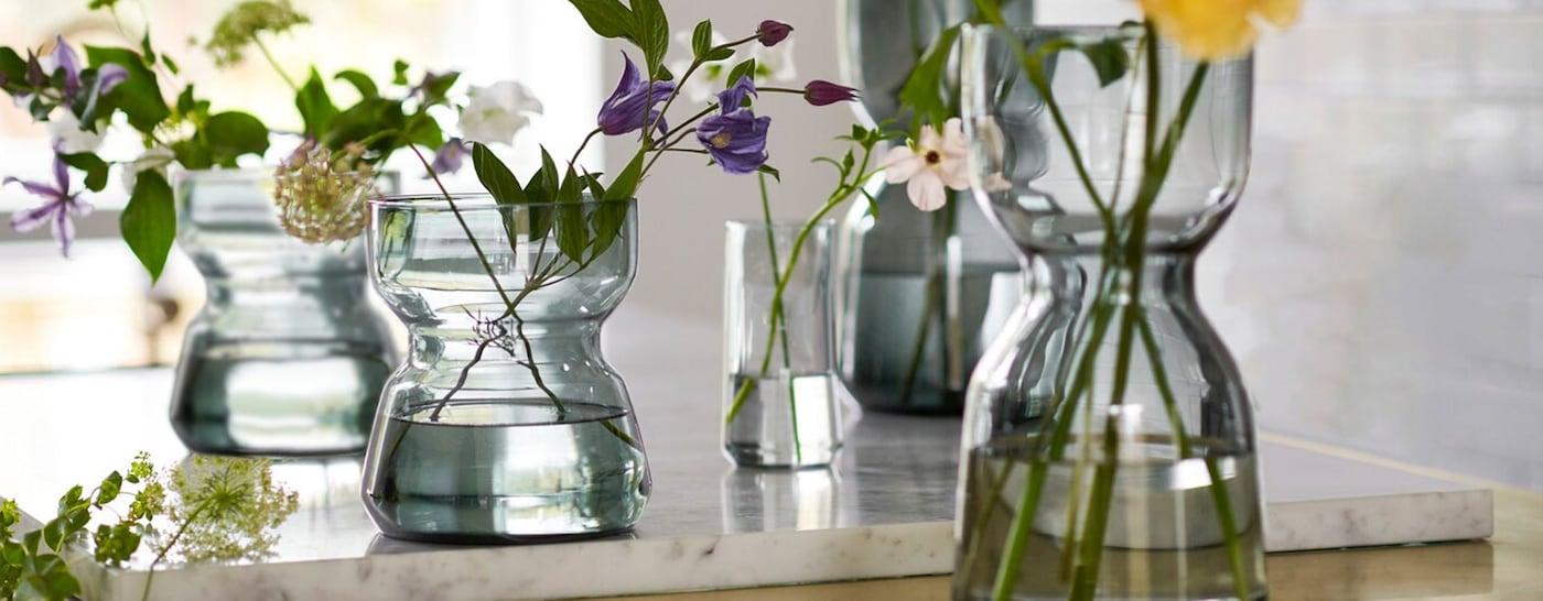 Meerdere glazen OMTÄNKSAM vazen met verse bloemen op een aanrecht, met een kenmerkende taille voor extra grip.