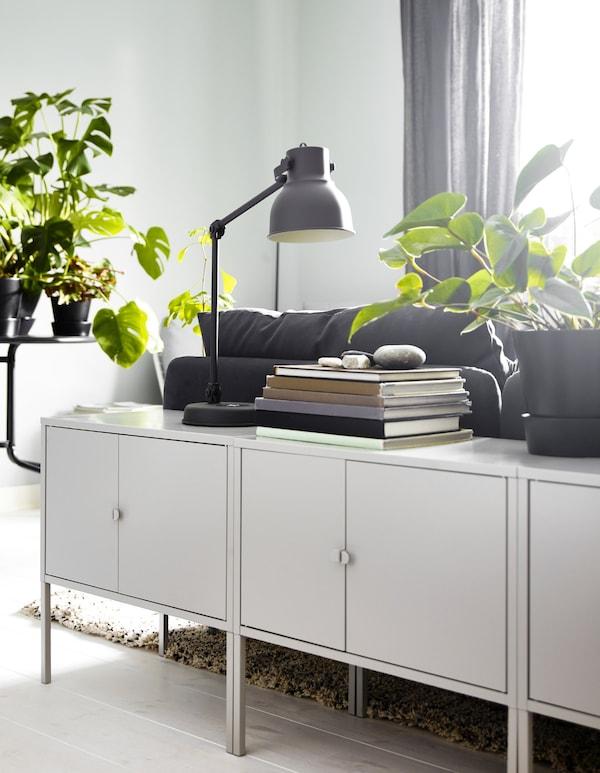 Meerdere IKEA LIXHULT kasten in grijs metaal achter een zitbank, met daarop een lamp en planten en boeken.